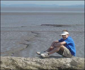 Toby sitting on a log on the foreshore near St Brides in Gwent (John Parker)