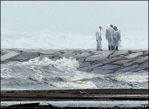 Local police investigate as they are reported a missing man as a powerful typhoon is approaching to the eastern Japan in Kujukuri, Japan, Wednesday, Oct 20, 2004