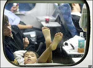 A child lies and places foot up against the window of a bullet train that is stranded at Nagoya station following a powerful typhoon Tokage in Nagoya, Wednesday, Oct 20, 2004