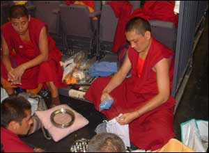 The monks select brightly coloured sand, which they have dyed in their monastery, to create the image.