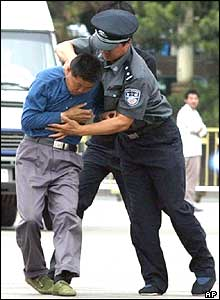 A Chinese policeman grabs a protester in Beijing's Tiananmen Square,  June 4, 2004