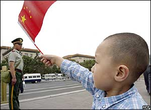 A young Chinese boy waves the national flag during a visit to Tiananmen Square in Beijing 04 June 2004