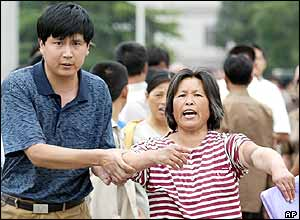 A Chinese woman yells and points to an injury on her arm as a plain clothed policeman detains her in Beijing's Tiananmen Square,  June 4, 2004