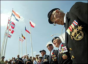 Fifteen D-Day veterans from the Royal Navy Tank Landing Craft pray for their colleagues in the square in Arromanches