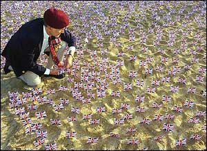 Raymond Daeche, from Harlow in Essex, plants a Union Jack flag in the sand on Sword Beach in Hermanville, Normandy