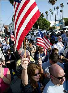 Cathy Bennett of Santa Monica waves an American flag as the hearse bearing the body of former US President Ronald Reagan arrives at the funeral home in Santa Monica.