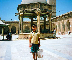 Young boy with his water bucket stands in courtyard of the Great Mosque in Aleppo, Syria