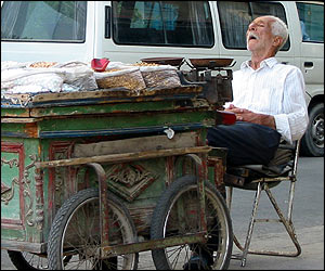 Man sleeps by his food cart on the side of the road in Damascus, Syria