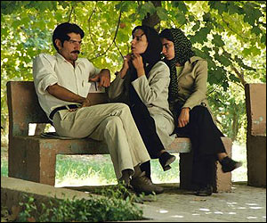 Man and two women sit on bench in Iran's Bagh-e-Eram