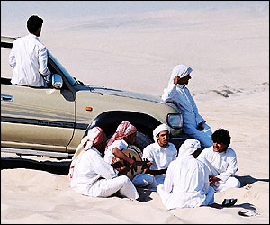 Qataris relax by their all-terrain vehicle in the sands of the Inland Sea