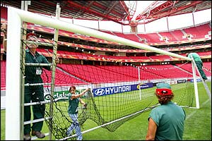Workers install goalnets at the Estadion Da Luz which hosts the Euro 2004 final on 4 July and England's opening game against France