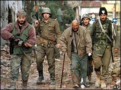 Yugoslav soldiers (background) and Serbian volunteers escorting a Croat civilian