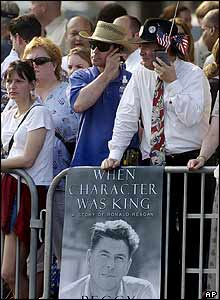 Spectators listen to radios as they watch the procession for former President Ronald Reagan,