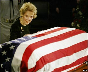 Nancy bends towards her husband's coffin