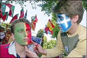 A Portugal fan gets his gets face painted by a Greece fan