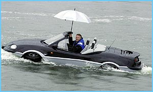 Branson in his amphibious car with a brolly out to stop sea spray!