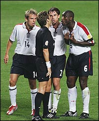 Phil Neville, Gary Neville and Sol Campbell argue with referee Urs Meier