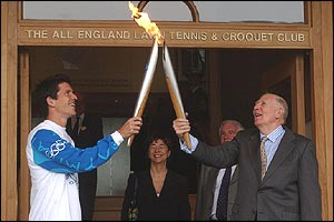 Sir Roger Bannister passes the flame to Tim Henman