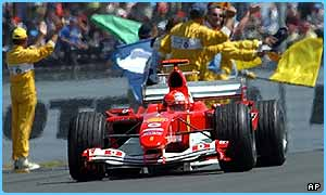 Michael Schumacher celebrates crosses the finishing line