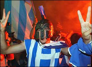A Greek fan celebrates outside City Hall early on Monday