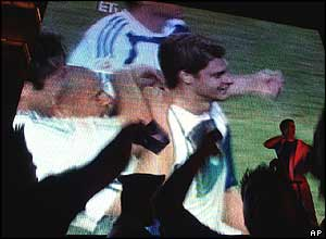 Greek fans react as Angelos Charisteas celebrates his goal on a video screen outside the Athens City Hall on Sunday