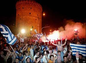 Greek fans in front of the White Tower, a landmark of the northern port city of Thessaloniki, Greece