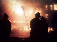 Silhouetted firefighters against blazing building