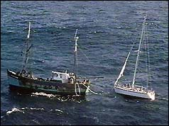 A stricken yacht is towed to safety