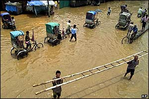 Rickshaws go through floodwaters in Gauhati