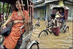 Rickshaw pullers take their customers through floodwaters in Gauhati