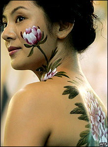 A model with body painting by Pang Guohua, a master of traditional Chinese painting, promotes his new book during Hong Kong Annual Book Fair