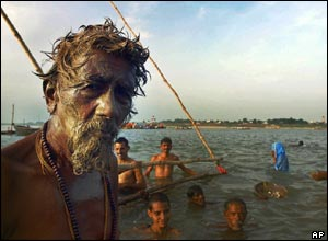 A Hindu holy man, with mud applied on his face, prepares to take a dip in the River Ganges in Allahabad, India