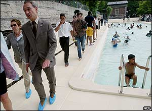 Paris mayor Bertrand Delanoe (left) walks past the new 28-metre pool, part of Paris's most popular summer attraction for the third year running