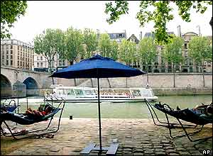 People relax in hammocks at the Paris Plage installation along the River Seine