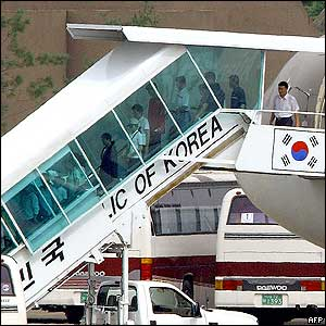 North Korean refugees get off an Asiana plane and move into buses, 27/07/04