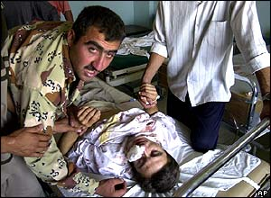 An Iraqi policeman tends to his injured brother in hospital