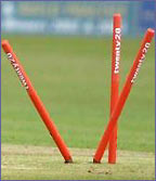 Three stumps are all over the place after a batsman is bowled