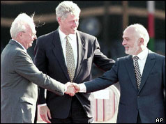 President Clinton smiles as Yitzhak Rabin (L) and King Hussein of Jordan shake hands