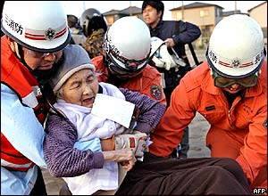 Elderly woman carried by rescue workers from a village at Nagaoka city in Niigata prefecture