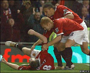 Wayne Rooney rolls on the pitch in delight as Paul Scholes and Rio Ferdinand come to congratulate him