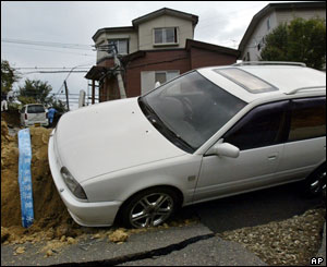 A car is caught in a crack on the road in Nagaoka, northwest of Tokyo, Monday, Oct. 25, 2004.