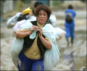 A woman carries a large load of belongings on her back in the muddy road in Ojiya, northwest of Tokyo, Monday, Oct. 25, 2004.