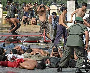 Thai policemen and soldiers arrest demonstrators at Takbai police station in Narathiwat, southern Thailand, 25 October 2004.