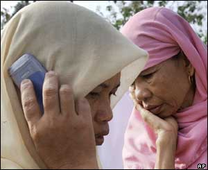 Two women, one calling home, after hearing the news that their family member is dead, Wednesday, Oct. 27, 2004.