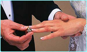 man putting wedding ring on woman's hand