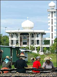 Thai Muslim women worker dry salted fish in the sun against the Narathiwat mosque in south Thailand 02 November 2004.