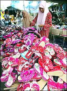 Thai Muslim women shop for sandals in a market place in Narathiwat province, south Thailand 02 November 2004.