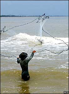 A Thai fisherman casts his net on a Narathiwat beach in southern Thailand, 02 November 2004.