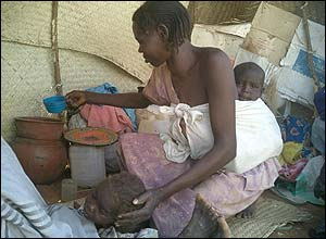 A woman gives her child water in a shelter in the new camp