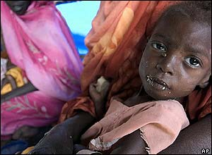 A mother and baby wait for food in Darfur